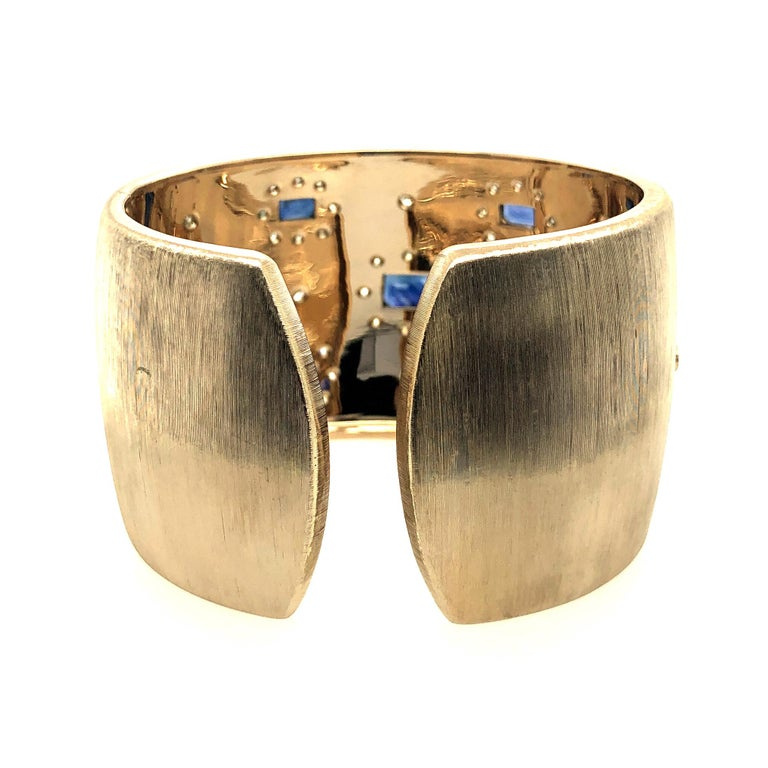 "Offered here is a gorgeous sapphire and diamond cuff bangle in 18kt gold. The cuff is extremely well made. The bangle is 18kt yellow gold ( marked 750 ITALY 2144M ). The bangle weighs 104.7 grams, measures almost 1.75"" wide and 7.25"" in length. The"