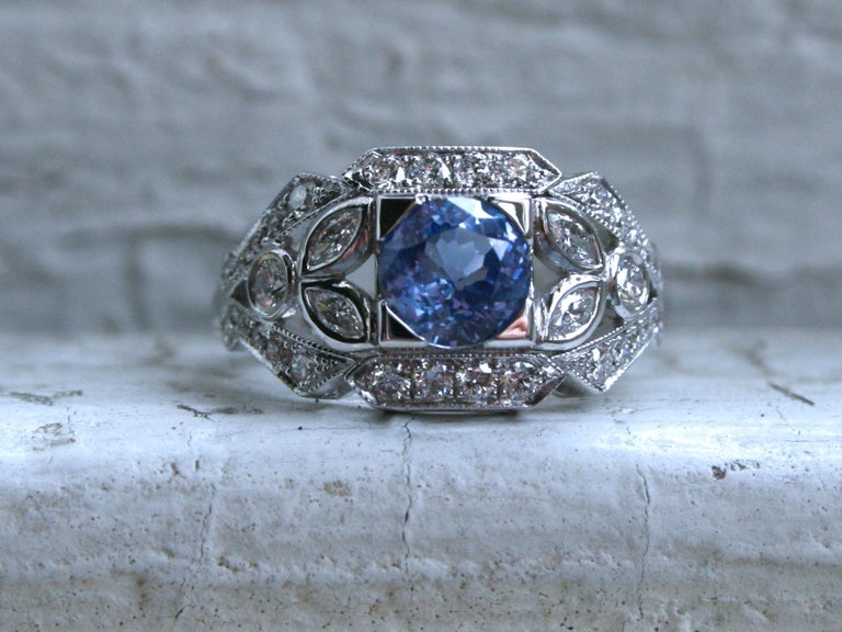 I LOVE the vintage design of this Round Sapphire Floral Diamond Ring Engagement Ring Wedding Ring! Simply stunning, and the sparkle is amazing! The design is a unique vintage floral design, with diamond studded open work, beaded edges, and a