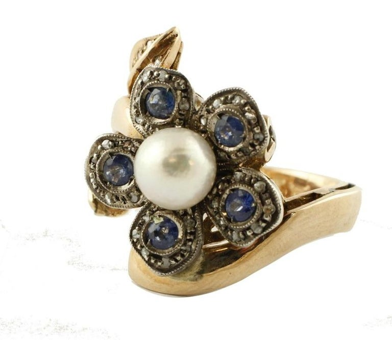 Charming fashion daisy ring, mounted in 14 Kt gold and silver, it is adorned of petals of diamonds and blue sapphires and in the middle a natural pearl. Ring Size: ITA 17 - French 57 - US 8 - UK Q Tot weight 13 Diamonds 0.25 Kt Blue Sapphires