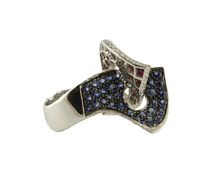 Fabulous 14 kt white gold ring, all enriched with sapphires, 8.74 ct rubies and 0.83 ct diamonds. Total weight g 15.25 Rubini sapphires ct 8.74 Diamonds ct 0.83 Size eng 16.5 Size franc 56.5 Size USA 7.75 Total weight g 15.25 RF + hhra  For any