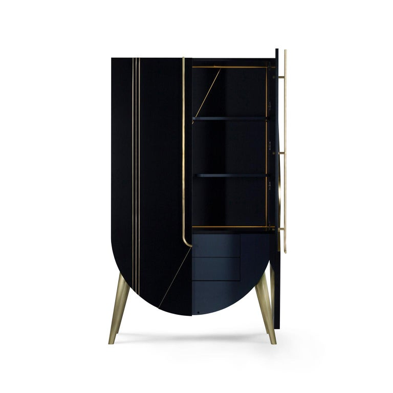 Wooden cabinet with a semi-round structure lacquered in satin black. Cabinet interior with drawers, shelf compartments and LED lighting triggered on the door opening. Handles, inlay metal details and legs in brushed brass with a high-gloss