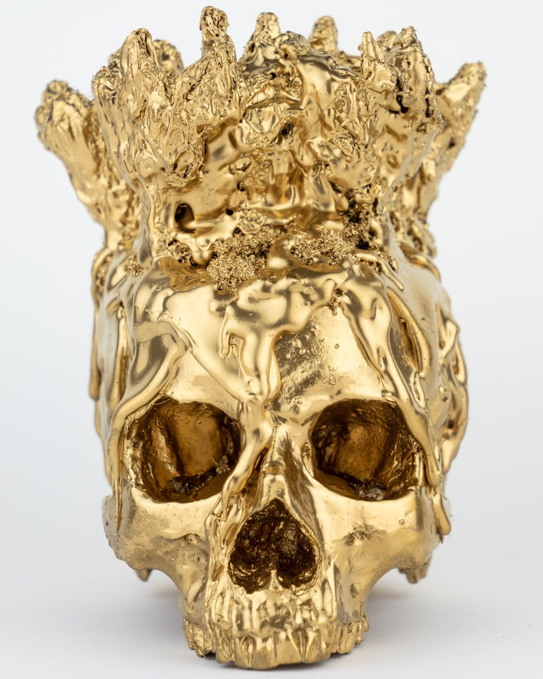 This Gold Skull Vase by Sarah Raskey is a 8 x 6.5 x 7 inch textured mixed media sculpture composed of natural and manmade elements.  A lustrous gold skull sculpture adorned with a headdress vase to fill with flowers etc.   Sarah Raskey is a