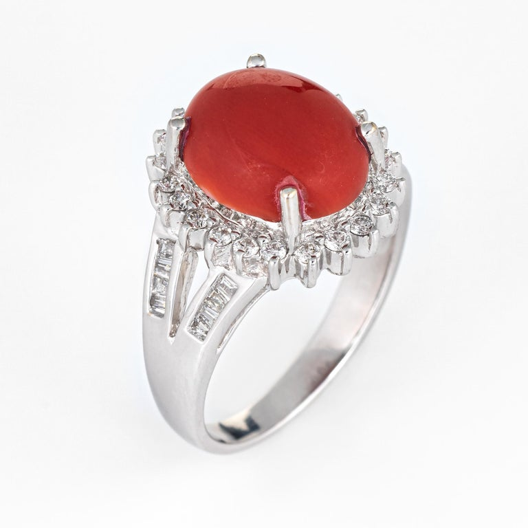 Stylish Sardinian coral & diamond cocktail ring crafted in 18 karat white gold.   Sardinian red coral cabochon measures 12mm x 10mm (estimated at 5.50 carats). The coral is in very good condition and free of cracks or chips. The diamonds total an