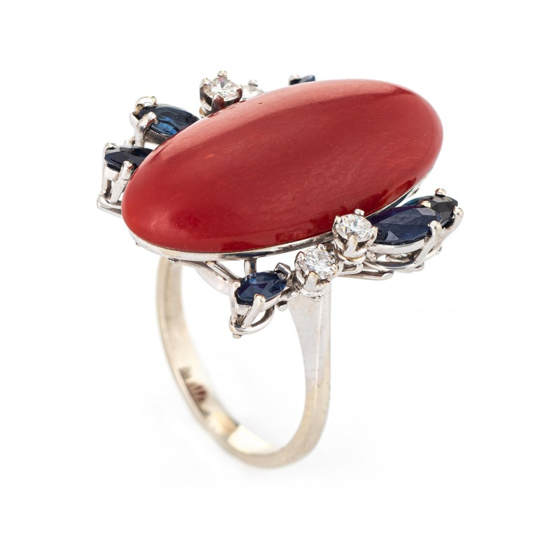 Stylish vintage Sardinian red coral, sapphire & diamond cocktail ring (circa 1950s to 1960s) crafted in 18 karat white gold.   Sardinian red coral measures 26mm x 12mm (estimated at 10 carats) is accented with 6 estimated 0.10 carats blue sapphires