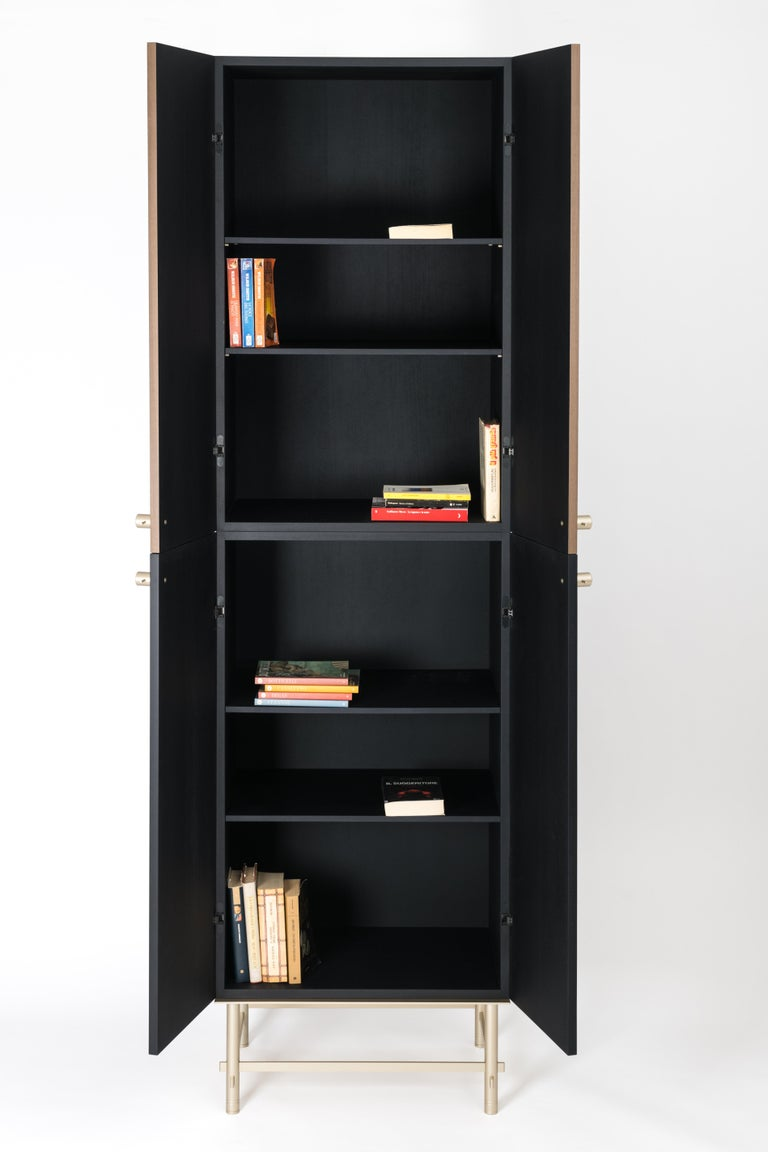 Closed cabinet in wood with doors: the external side in wood - two color finishing, the internal side in wood - one color finishing, lifted above the ground by means of a metallic interlocking structure. Handles in metal with wood insert and five