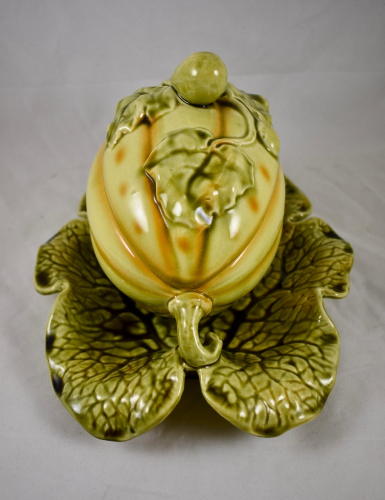 A French majolica covered tureen in the shape of a trompe l'oeil melon by Sarreguemines, circa 1900.  Molded in the form of a large yellow melon with green vines and leaves. The lid is decorated with leaves and a top knob molded as a small melon.
