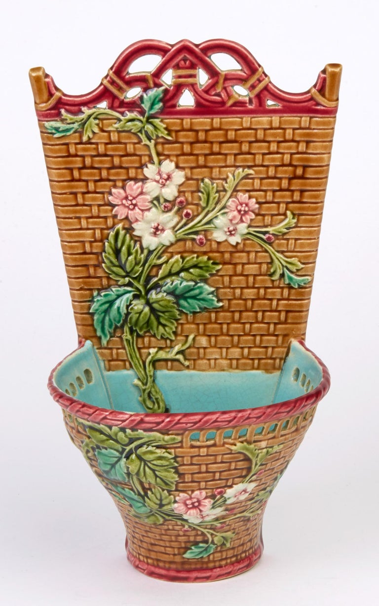 A very fine antique French art pottery Majolica wall pocket by Sarreguemines and dating from circa 1880-1890. The lightly pottery wall pocket is modeled as a basket with a pierced rim containing flowers which are applied to the front and to the back
