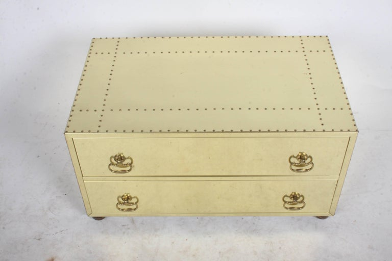 Brass clad studded chest in the style of Sarreid, circa 1970s or early 1980s. Two-drawer chest on bun ball wood feet. Minor scuffs and a ding, expected with age. Compliments Mastercraft Furniture. Please note very reflective, shows dirt from paper