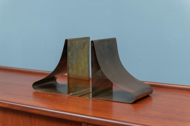 Sarried decorative brass bookends, large and sculptural design able to hold larger size books, labeled.