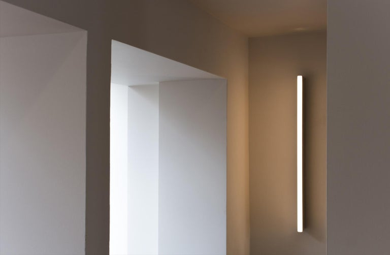 The tube wall light, a rectangular fixture illuminating from a slender light in front, adds a sleekness to any residential or commercial space. Satin brass finish. Design patented in 2006.   Michael Anastassiades' design philosophy is to preserve