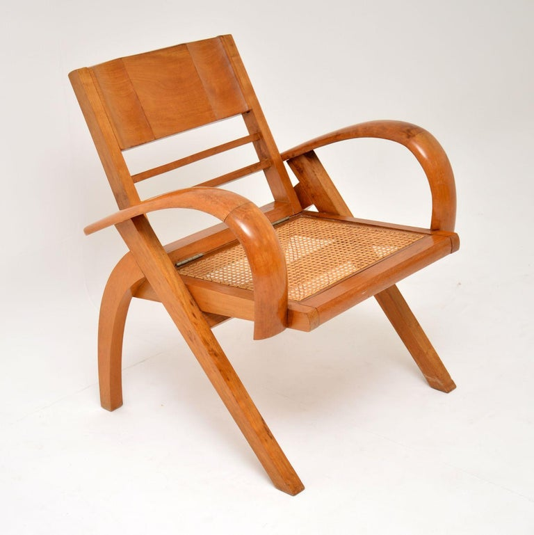 A stylish and unusual vintage armchair in solid satin wood, dating from the 1960s-1970s. The previous owners had the seat re-caned, the frame is clean and sturdy. There is some minor wear here and there, seen in the images. The back is hinged and