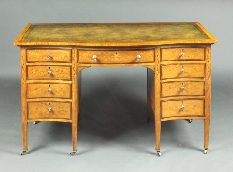 Satinwood inlaid dressing table by Edwards and Roberts An attractive satinwood dressing table/desk: inlaid floral decoration with ribbons and swags; standing on tapered legs with brass castors; green leather top and original silvered knobs (one