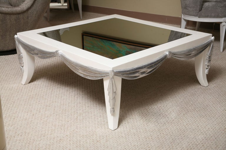 Very unusual coffee table. Wood frame in white lacquer with sculpted draping in silver leaf. The top has a mirror inset.