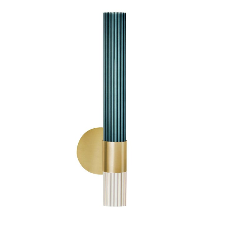 Refined and timeless, this sconce is part of a collection named with the Milanese word for sparkle. This magnificent piece of functional decor is handmade by skilled craftsmen in Brianza, near Milan, and comprises a champagne gold metal base and