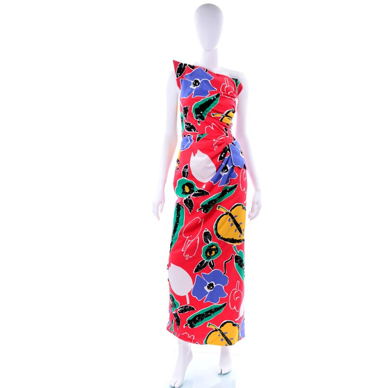 This is a stunning vintage dress from Arnold Scaasi in a gorgeous red, blue, yellow, green and white cotton floral print.  The pattern of the fabric is embellished with sequins and we especially love the asymmetrical bust line!  There is a metal
