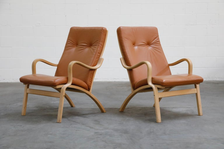 A nice set of two (2) Scandinavian Bentwood leather lounge chairs and one (1) ottoman, priced as a set. Nicely sculpted birch frames with curvaceous arms and brown leather cushions. Well made, great quality materials and craftsmanship, very good