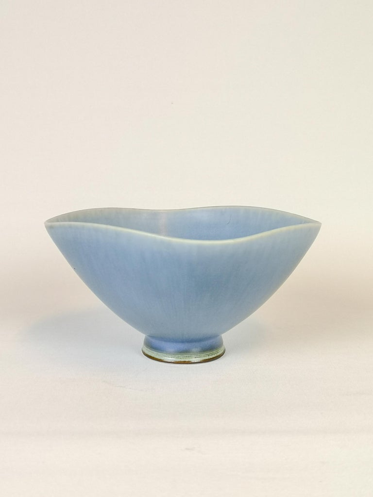 This bowl has everything working for it. Wonderful sculptured and with a stunning glaze that shifts in color.  It was made by Berndt Friberg at Gustavsberg Studio and is marked in the bottom.   Very good condition.   Measured H 7 cm D 15