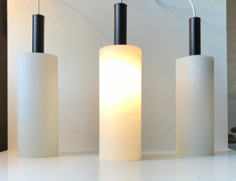 A trio of 'hammer' or 'mallet' shaped pendant lamps composed of matté cased opaline glass and top made from powder coated steel. Designed and manufactured by Lyfa in Denmark during the 1970s in a style reminiscent of Stilnovo.