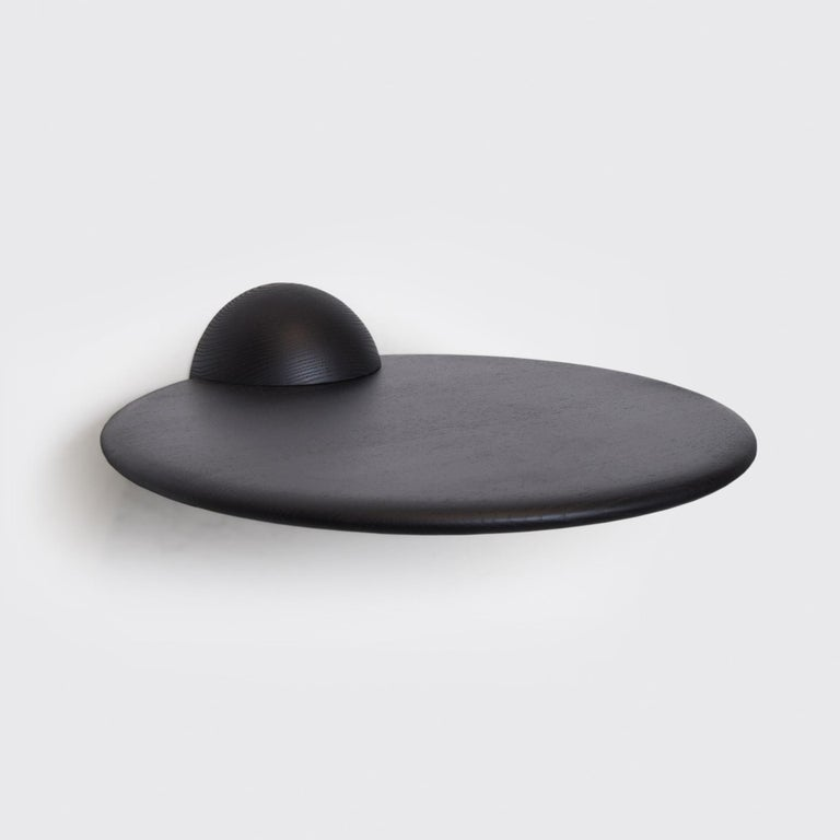 The half sphere holding the plane contributes to a bold yet minimal look that works well in several different spaces and environments. Whether used as a shelf for an extraordinary object, as a bedside table or as a small bar table it's present with