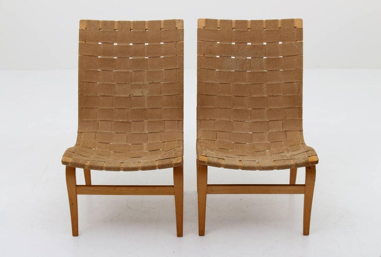 "Gorgeous pair of ""Arbetsstolen"" lounge chairs by Bruno Mathsson for Karl Andersson & Söner, Sweden, 1940s. This early pair is made with paper webbing, due to loss of hemp during the Second World War. Condition: Great original condition with perfect"