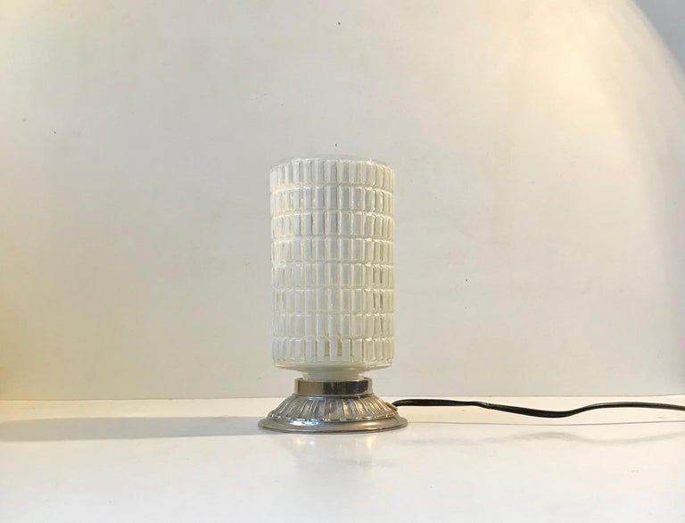 Small and unusual table light with a checkered glass shade and an aluminium base. These type of lights originally went under names as restaurant lamps or 'Dating lamps' and was intended to replace the candlesticks under dim lighting. It was made in