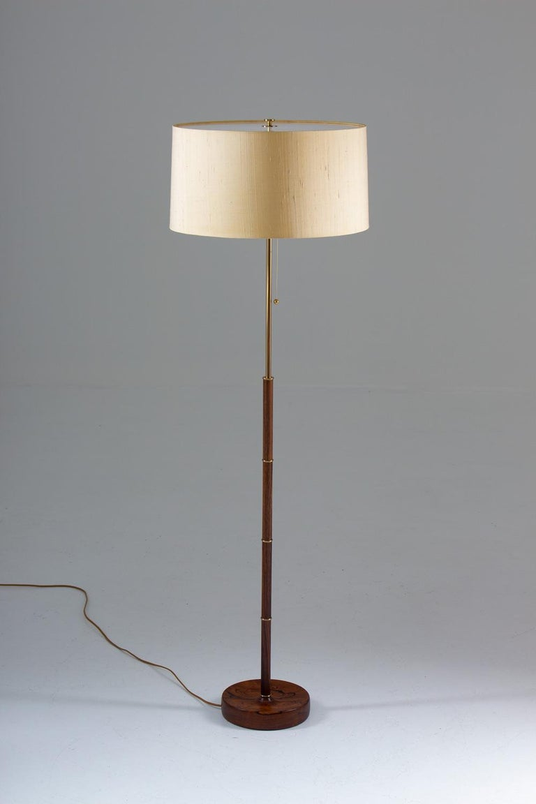Scandinavian midcentury floor lamp model G-04 in brass and rosewood by Bergboms, Sweden, 1960s. This rare lamp is made of solid, beautifully carved rosewood and brass. It comes with its original shade, which rests on a white transparent plexiglass