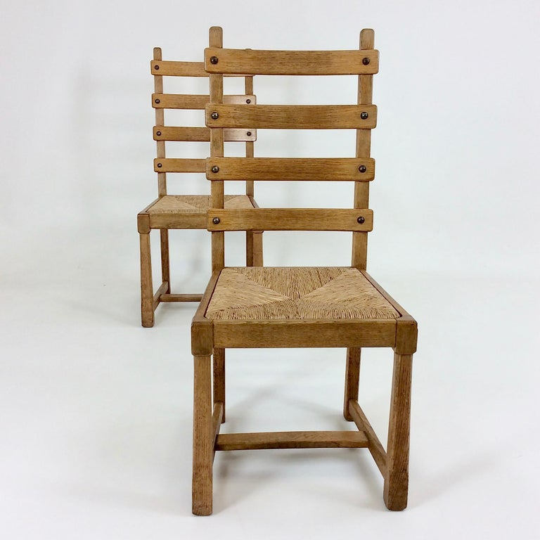 Elegant pair of Scandinavian chairs, circa 1950, Scandinavia. Oak, straw seat. Dimensions: 103 cm H, 47 cm W, 50 cm D, seat height 45 cm. Two other pairs available. Good original condition. All purchases are covered by our Buyer Protection