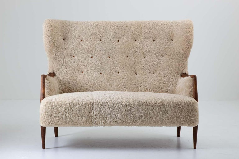 Stunning 2-seat sofa / loveseat produced in Denmark, circa 1940. This wingback sofa is constructed with an impressive quality. The proportions and shapes are made with a great sense for design and the wooden details contribute to the exclusive