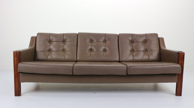 Scandinavian design three-seat comfortable sofa made in late 1960s-early 1970s. High quality leather seating and rosewood frame. Good vintage condition. Patinated with signs of wear consistent with age and use. In a style of Hans J. Wegner.