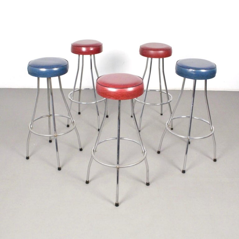 Scandinavian midcentury bar stools made in chromed tubular steel frame. Red (3) and blue (2) skai leather upholstered seats.