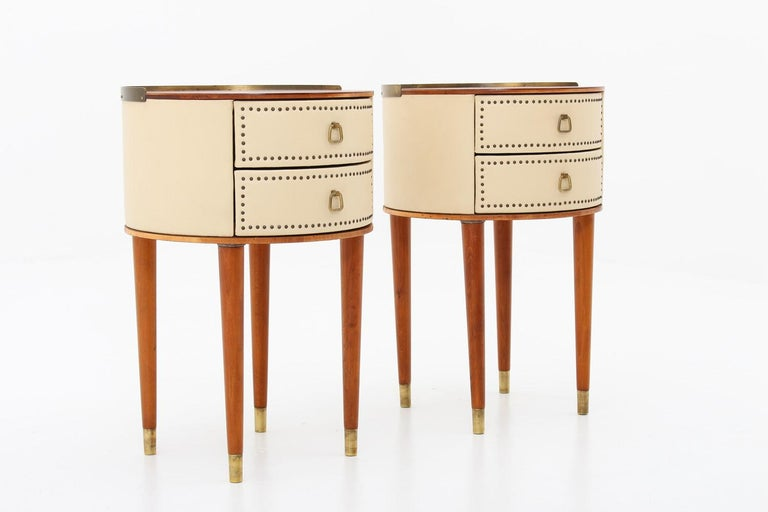Designed by Halvdan Pettersson for Tibro Möbelfabrik, circa 1940. These round bedside tables are covered with cream white faux leather with brass details. The table top is made of mahogany and the legs of stained beech. Condition: Very good