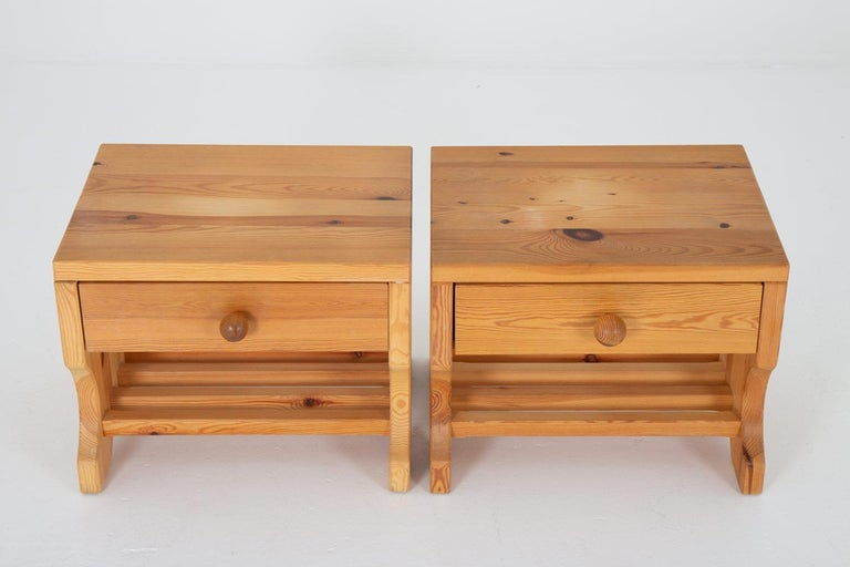 A pair of bedside tables by Stig Höglunds Träsvarveri, 1970s. These bedside tables are made of solid pine with great details, such as the visible joinery and the round handles.  Condition: Good original condition. Light signs of age and use, a