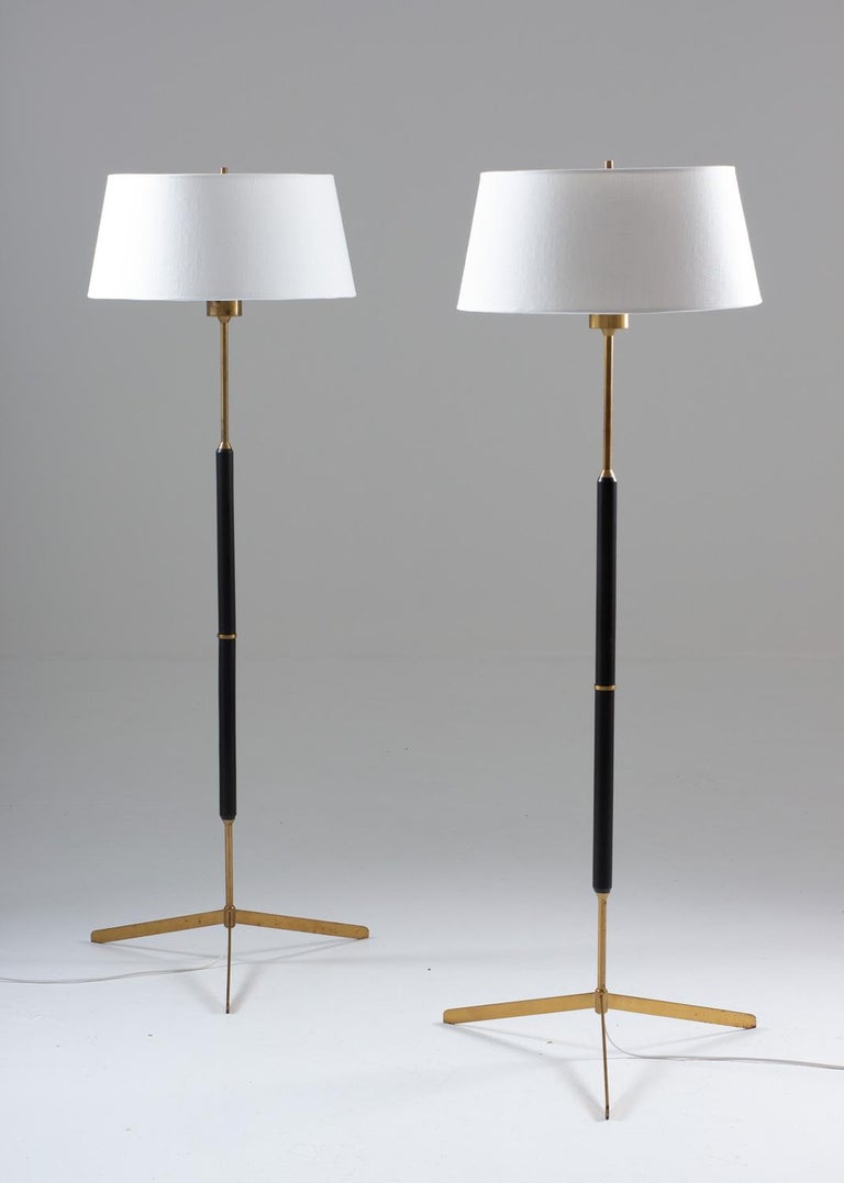 Scandinavian midcentury tripod floor lamps in brass and wood, model G-31 by Bergboms, Sweden, 1950s. These lamps are made of solid brass, with details of black painted wood. The lamps come with their original shades, which have been restored with