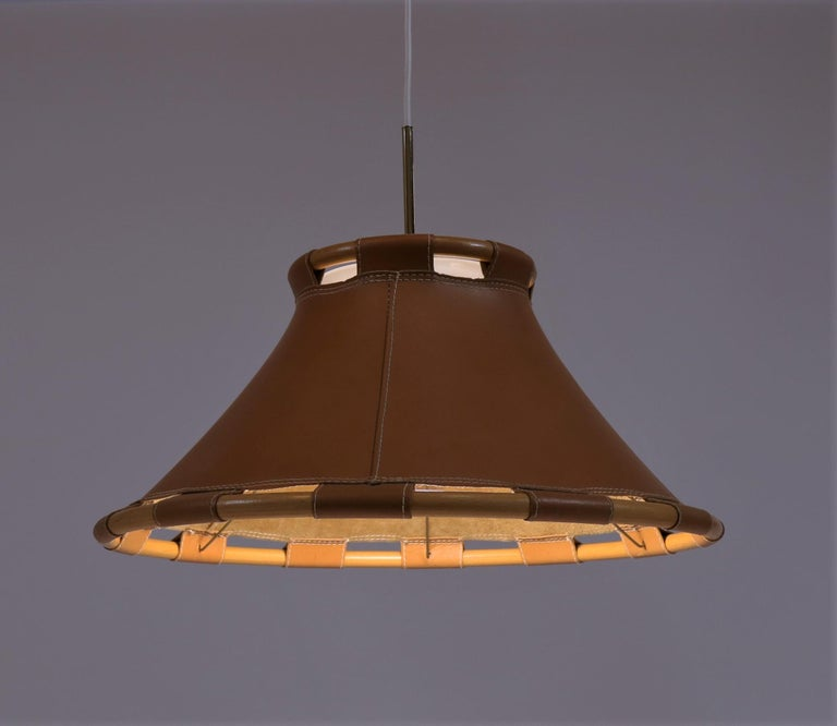 Amazing Swedish design by Anna Ahrens for Ateljé Lyktan, Sweden, 1970s. The shade is made from saddle leather and bent beech with nice brass details and an acrylic diffuser. The lamp has been rewired with white fabric cord.
