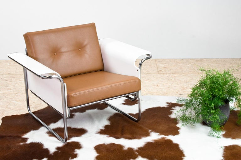Scandinavian Modern armchair new upholstered in a tan colored faux leather upholstery. The flared armrests are made of (white lacquered) bent plywood, placed in a chromed metal tubular frame that without a doubt was inspired by the Bauhaus