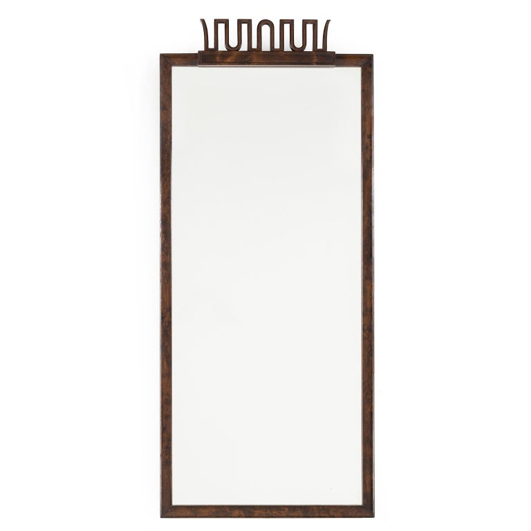 Scandinavian Modern, elegant Swedish Art Deco mirror by Axel Einar Hjorth for NK (Nordiska Kompaniet) Stockholm circa 1920s. The frame is stained and polished birch with a stylized carved wood