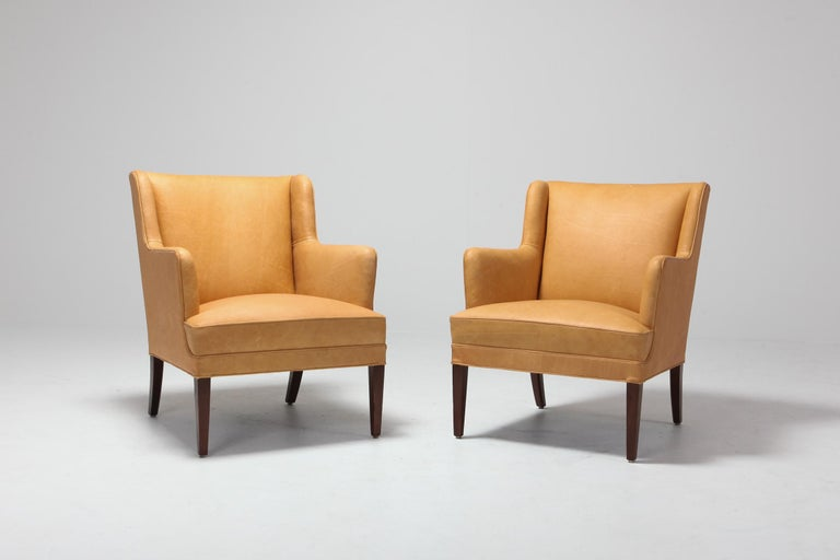 Mid-Century Modern armchairs in camel colored leather  Reminds a bit of the designs of Nanna Ditzel and Arne Norell.