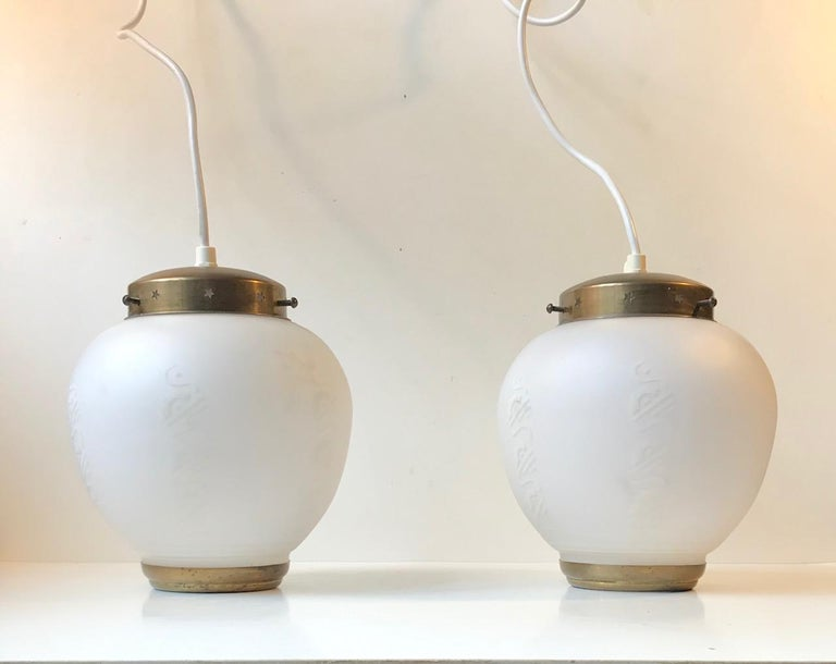 A pair of Scandinavian ceiling lights manufactured and designed during the 1950s. Probably by Lyfa in Denmark. However they remain unattributed. They are made from patinated brass and have a center shade in partially decorated white milk or opaline
