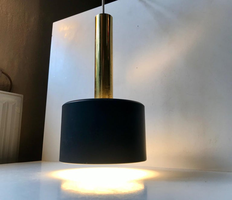This Scandinavian pendant light made from brass and dark grey powder coated aluminium. At first glance it looks similar to Jo Hammerborg's 'Club' pendant for Fog & Morup. This one is slightly different. It was manufactured during the 1960s probably