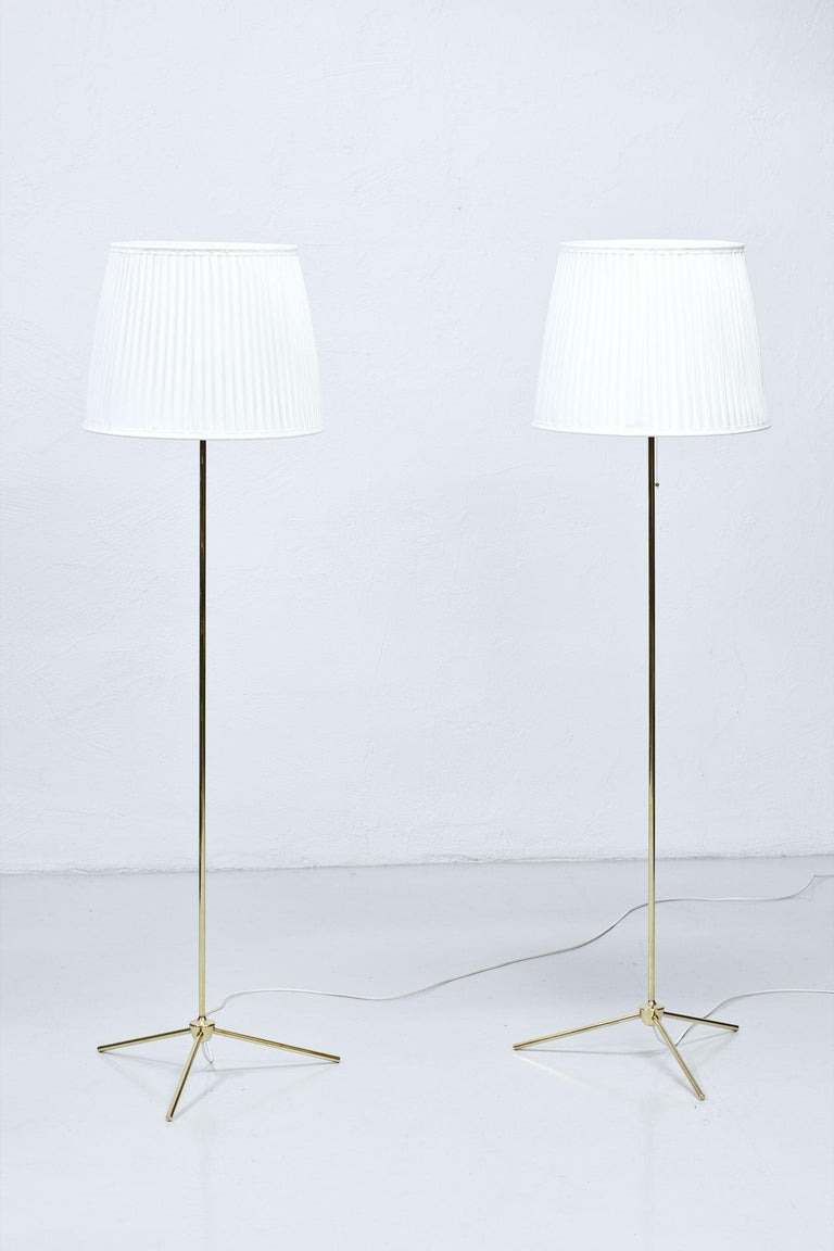 """Rare pair of floor lamps model """"G-302? manufactured by Bergboms in Sweden during the 1950s. Polished brass stem. New hand sewn, off–white pleated chintz fabric shades. Rewired."""