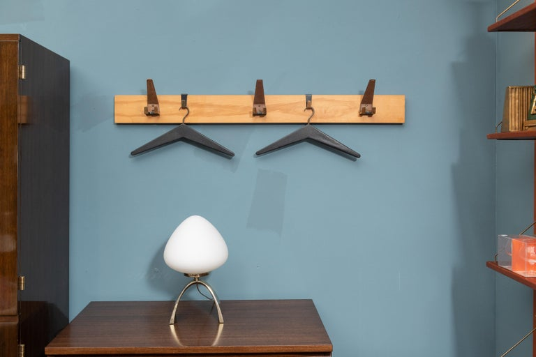 Scandinavian Modern coat rack with two hangers that slide back and forth and three leather wrapped brass coat hooks.