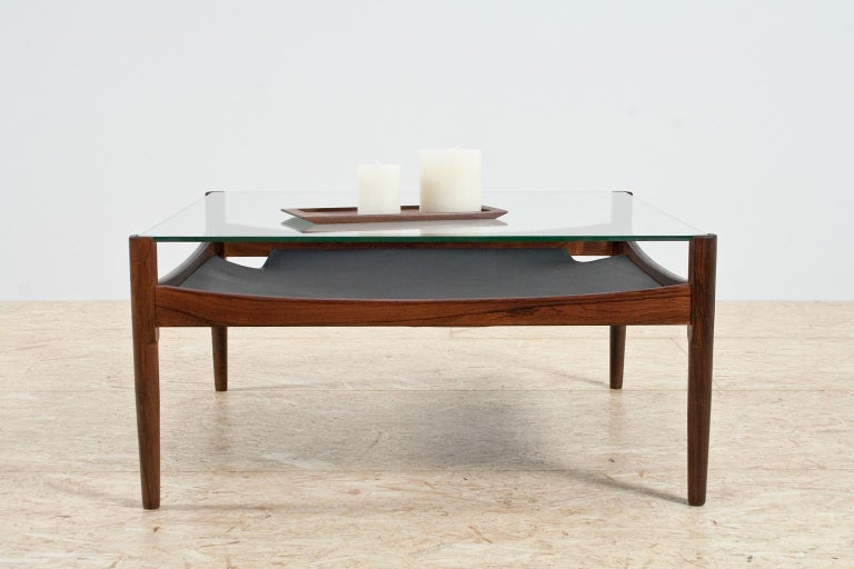 Midcentury and Scandinavian Modern coffee table by Kristian Vedel for Søren Willardsen in Denmark, 1960s. The table is made of solid rosewood, 8mm/ 0.31 inch thick glass in good condition and a black leather magazine rack underneath. The table is in