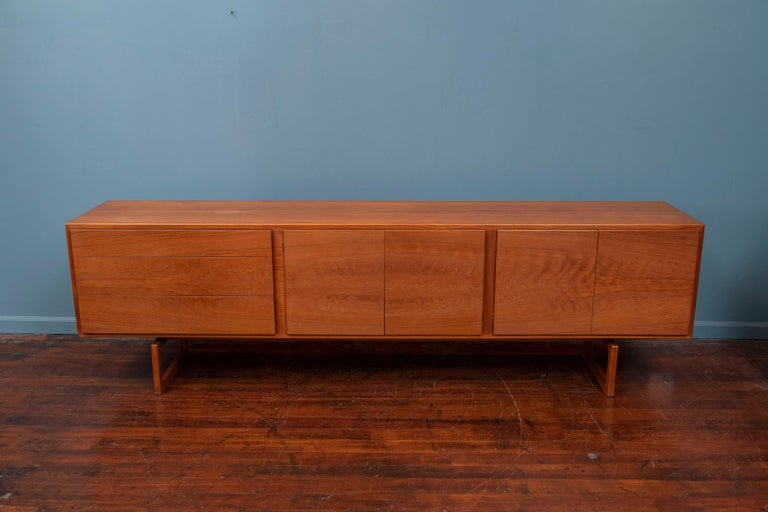 Rare Danish credenza model: MK511 designed by Arne Hovmand Olsen for Mogens Kold. Gorgeous Minimalist modernist design in solid teak. The entire front of the cabinet is made from a single piece of teak which results in a gorgeous bookmatched grain