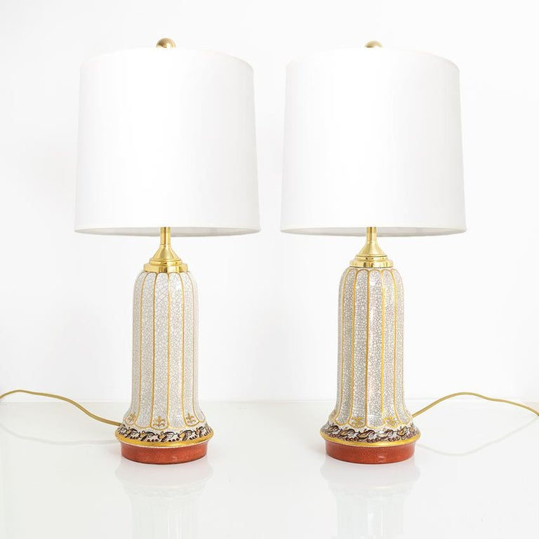 Two matching Scandinavian Modern porcelain lamps designed by Jens Peter Dahl-Jensen and produced by his company Dahl-Jensen, Copenhagen, Denmark. The lamps have fluted bodies in a crackle glaze and are trimmed in gold. The base has a coral colored