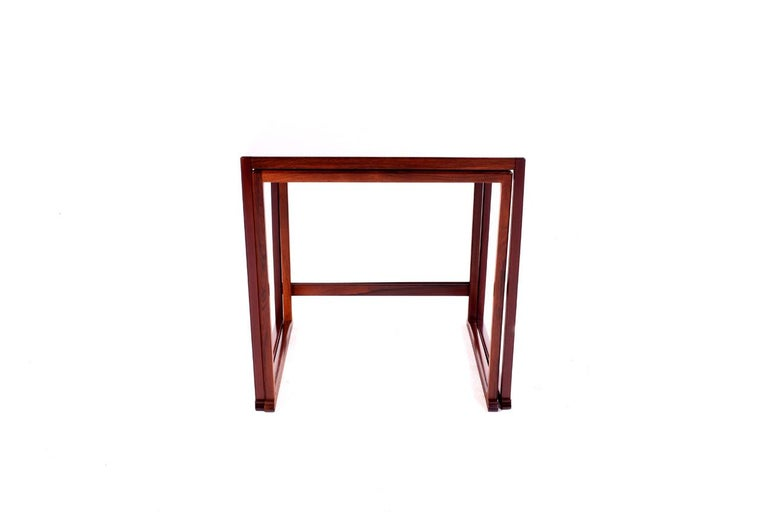 Nice set of two nesting tables rectangular. The rosewood veneer wraps over the surface and around the edges, with rectilinear rosewood frame