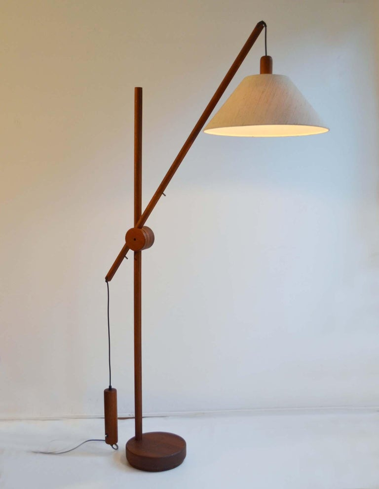 Scandinavian Mid-Century Modern floor lamp with teak frame has an adjustable arm with counterbalance weight for perfect positioning of the light. The lamp is engineered with a lot of functional details. The original shade and frame are in perfect
