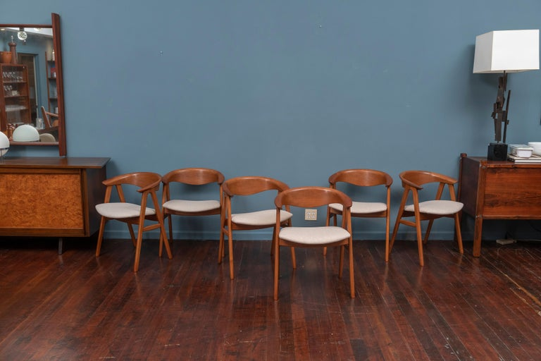 Scandinavian Modern Erik Kirkegaard design set of six teak dining chairs with newly upholstered wool felt seats. The sculptural form frames are beautiful to look at as well as very comfortable to sit in.  The frames have been newly cleaned and