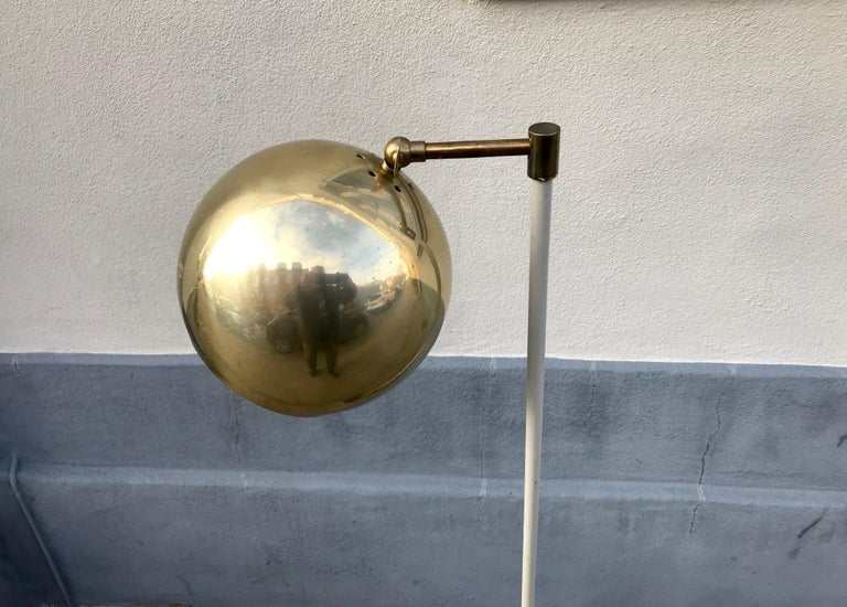 Unusual Scandinavian floor lamp with an adjustable spherical shade in brass. Anonymous maker/design in the style of Verner Panton and Stilnovo. The shade is adjustable up/down and from side to side. Measures: Height 125 cm. Shade diameter 20 cm.