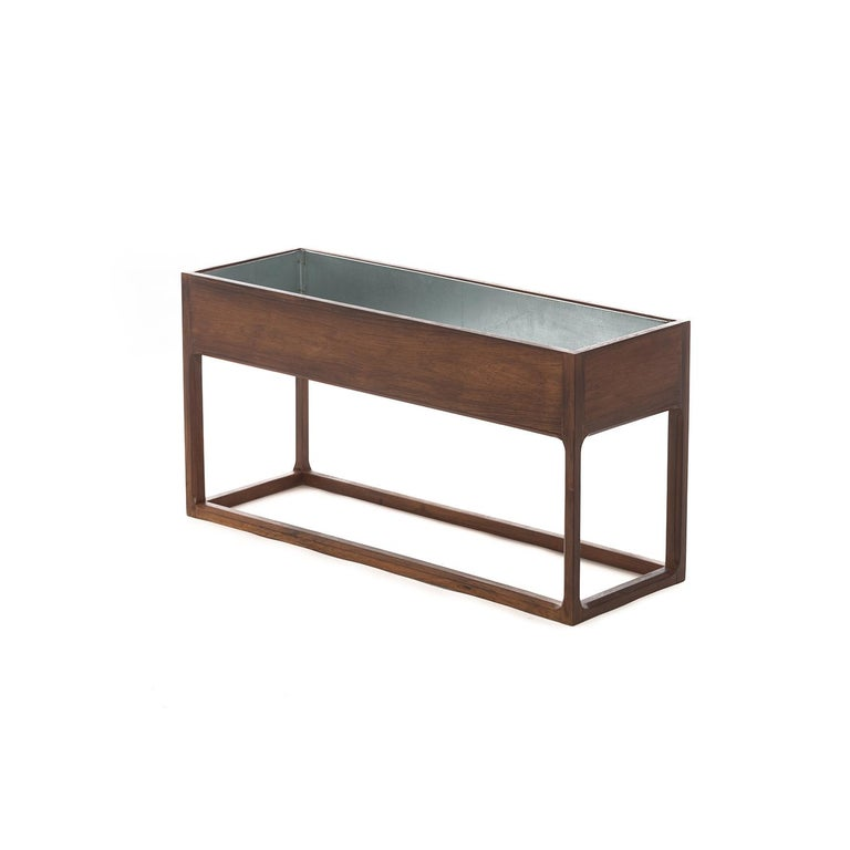 This elegant planter features a frame style base with a jewel-cutout detail on the inner legs. Rosewood is deeply figured and finished in a durable lacquer, which has been updated. Aluminum liner is removable for easy cleaning. Perfect to set pots