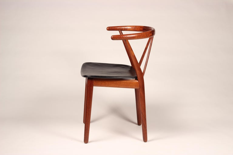 One dining chair/ desk chair model 255, in teak and leather by Henning Kjærnulf for Bruno Hansen, Denmark, 1950s. These solid teak chairs have a beautiful curved back. The diagonal support of the back makes the design of these chairs very open and